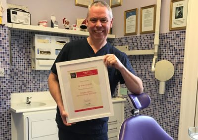 Dr Brian McEniff holding Caring Dentist of the Year Award 2018